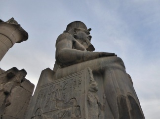 One of two remaining (out of six) colossal statues of Ramses II that guard the gates to the temple. Photo by Tricia.